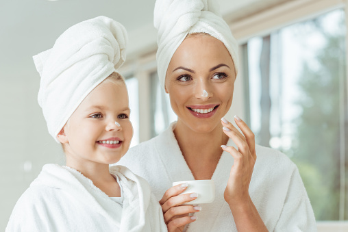 istock mother and daughter applying face cream 900833048