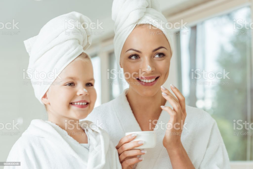mother and daughter applying face cream stock photo