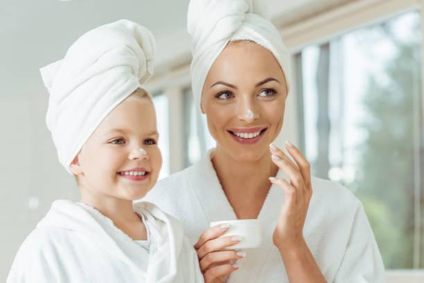 母と娘の顔のクリームを適用します。 ストックフォト