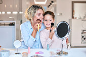 Mother and daughter putting on make up, putting powder with powder brush