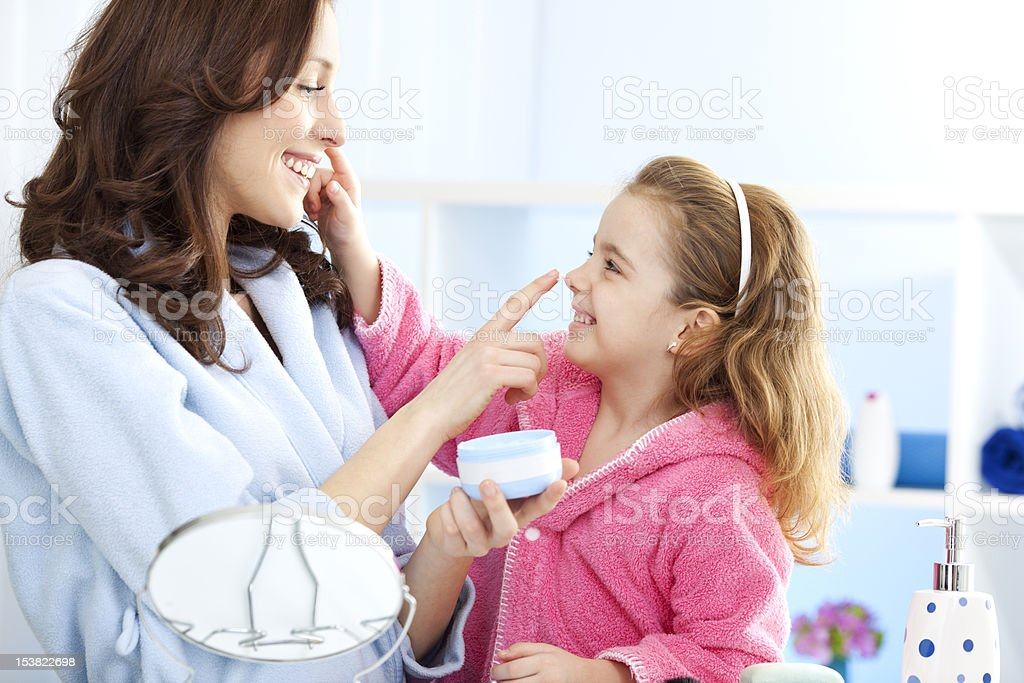 Mother and daughter applying moisturizer face cream stock photo