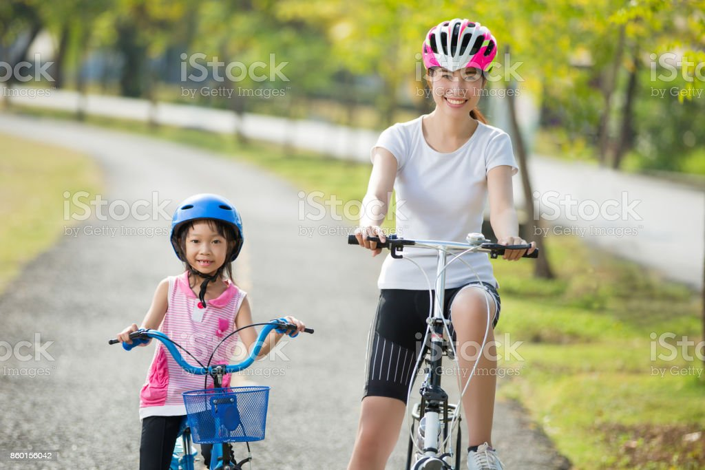 Mother and daughter are biking to the park stock photo