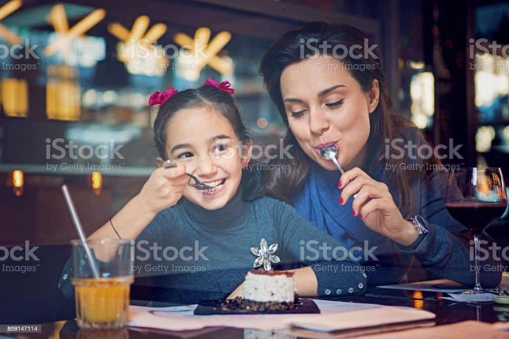 Mother and daughter are eating a cake in the cafe stock photo