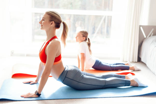 Mother and daughter are engaged in yoga in sportswear. They are in a bright room with panoramic windows. Mother and daughter are engaged in yoga in sportswear. They are in a bright room with panoramic windows. They are in bhujangasana asana, cobra pose. cobra pose stock pictures, royalty-free photos & images