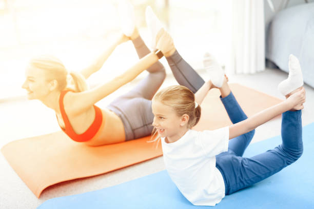 Mother and daughter are engaged in yoga in sportswear. They are in a bright room with panoramic windows. stock photo