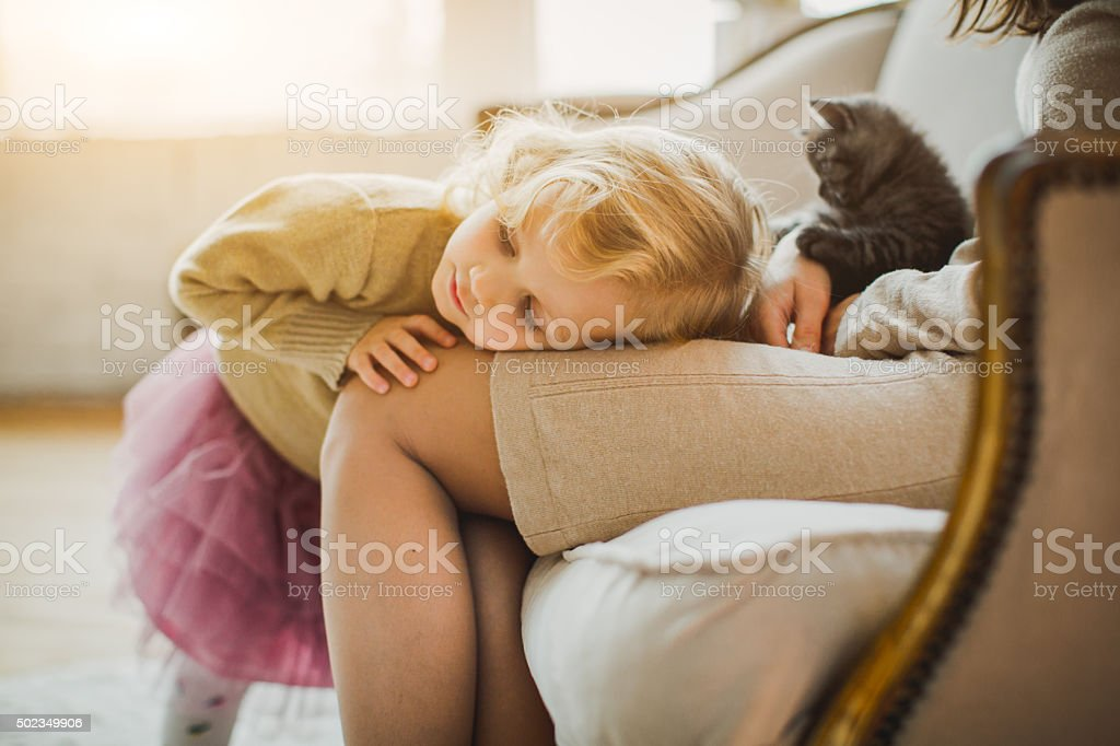 Mother and daughter are playing with kitten stock photo