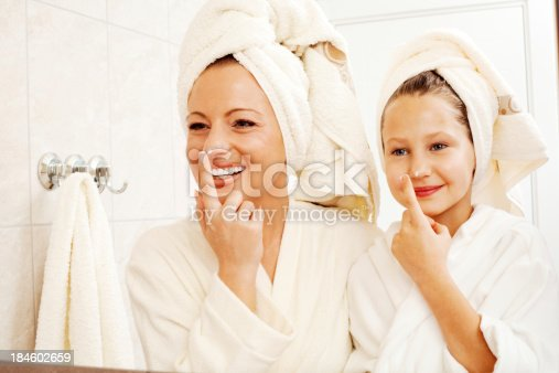 Beautiful mother and her daughter are putting on moisturizing cream on their nose.