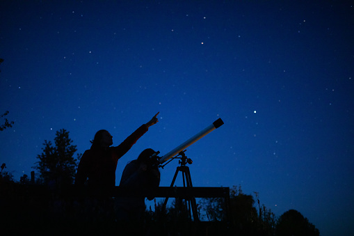 Mother observing stars on the night sky with daughter standing on the viewpoint. Daughter looking stars through the telescope and the mother points with finger in which direction should looking.