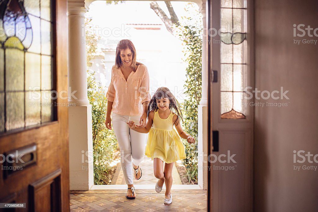 Mother and daughter arriving home through their front door stock photo