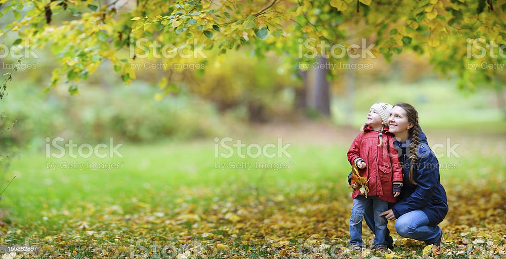 Mother and daughter at autumn park stock photo