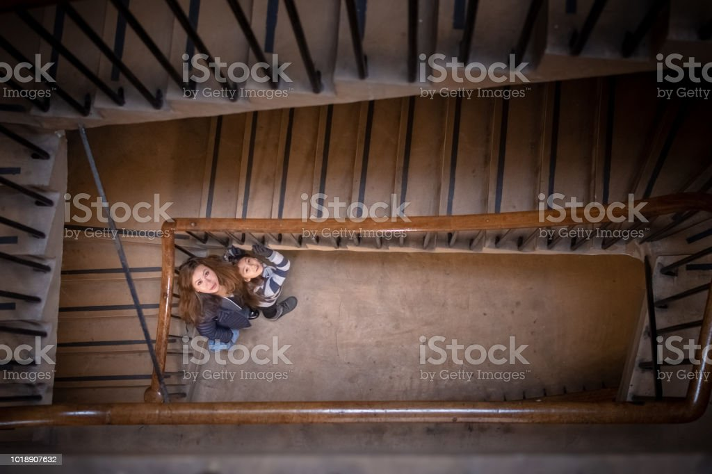Mother and daughter at bottom of apartment stairwell in Edinburgh, Scotland stock photo