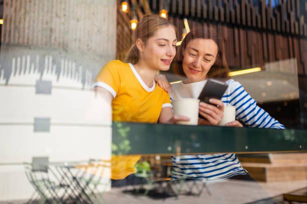 Mutter und Tochter im Café schauen zusammen auf Handy – Foto