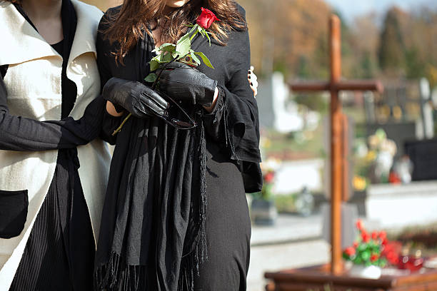 mother and daughter at cemetery - funeral crying stockfoto's en -beelden