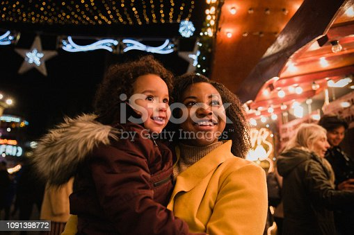 A close-up front-view shot of a woman holding her young daughter, they are both looking at bright Christmas lights at the Christmas markets on a cold night, the young girl is in awe.