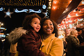 A close-up front-view shot of a woman holding her young daughter, they are both looking at bright​ Christmas lights at the Christmas markets on a cold night, the young girl is in awe.