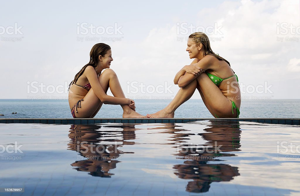 Mother and daughter at edge of pool  12-13 Years Stock Photo