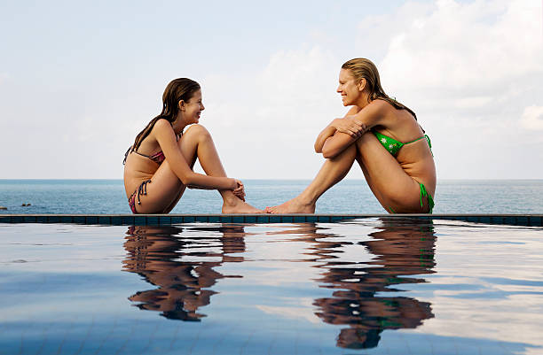 Mother and daughter at edge of pool stock photo