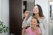 Happy Latin American mother and daughter at home brushing their teeth in the bathroom - lifestyle concepts