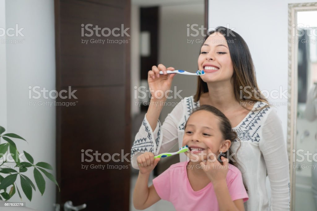 Mother and daughter at home brushing their teeth stock photo