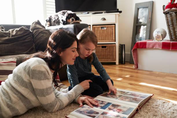 Mère et fille à la maison à la recherche grâce à l'Album Photo - Photo