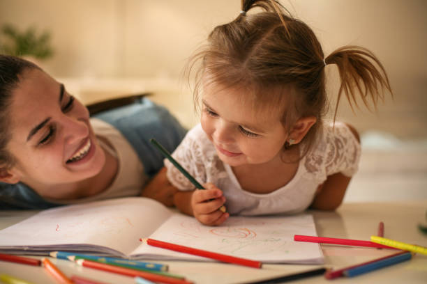 mother and daughter at home. mother teaching her daughter to drawing and writing. - colouring book stock photos and pictures