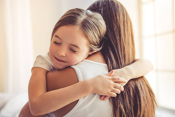 mother and daughter at home - hug bildbanksfoton och bilder