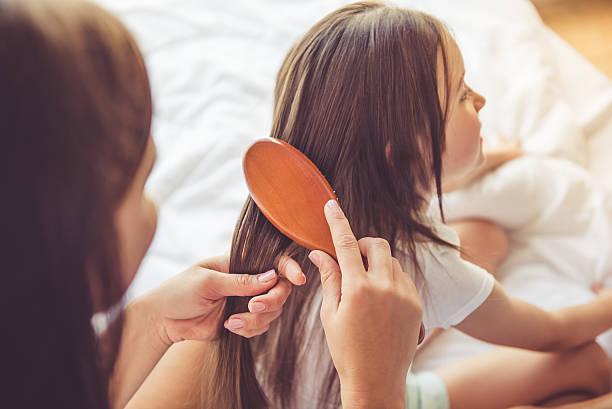 Mother and daughter at home Charming little girl is smiling while her beautiful young mother is combing daughter's hair combing stock pictures, royalty-free photos & images