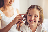 Charming little girl is looking at camera and smiling while her beautiful young mother is combing daughter's hair