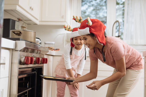 mother and daughter at home - christmas cooking foto e immagini stock