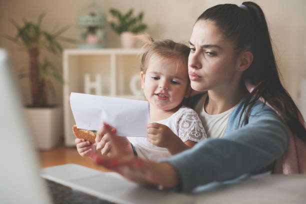 mother and daughter at home. woman reading her bills. - holiday and invoice family foto e immagini stock