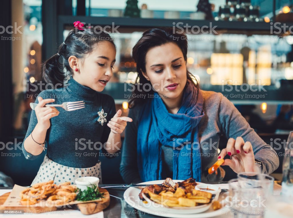 Mother and daughter at restaurant stock photo