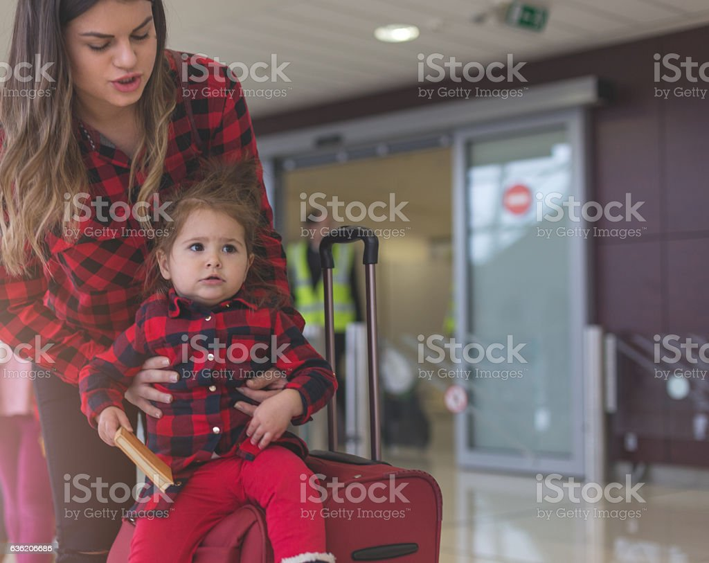 mother and daughter at the airport door stock photo