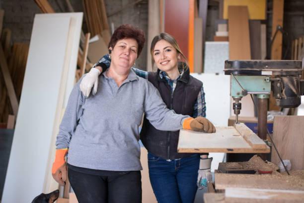 mother and daughter at woodworking workshop - pais e filhos imagens e fotografias de stock