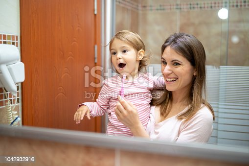 istock Mother and daughter baby girl brushing their teeth together 1042932916
