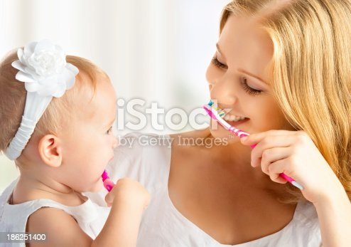800444456 istock photo mother and daughter baby girl brushing their teeth together 186251400