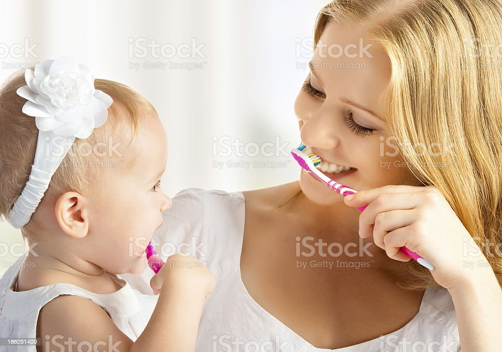 mother and daughter baby girl brushing their teeth together stock photo