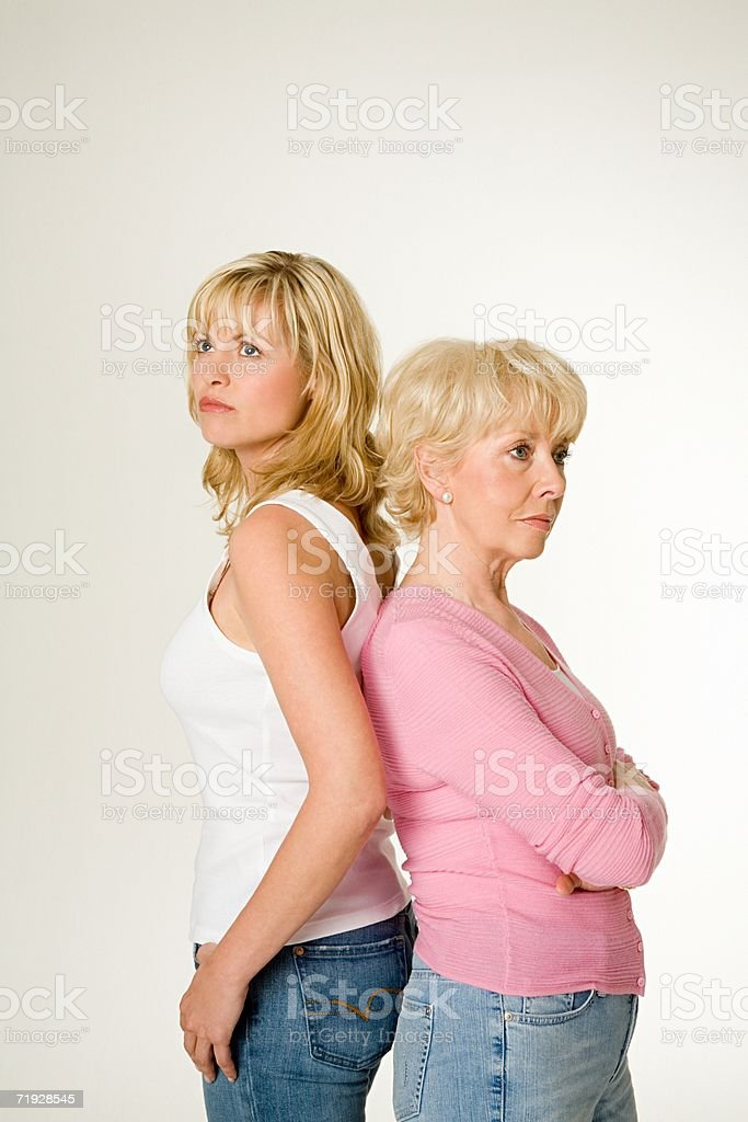 Mother and daughter back to back royalty-free stock photo