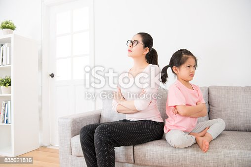 istock mother and daughter back to back sitting on sofa 835621816