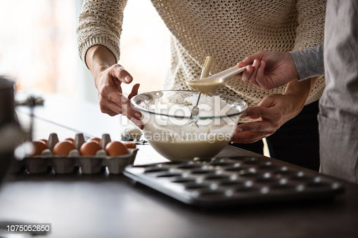 Close-up shot of mid adult woman and her daughter scooping batter into muffin tin at the kitchen counter.