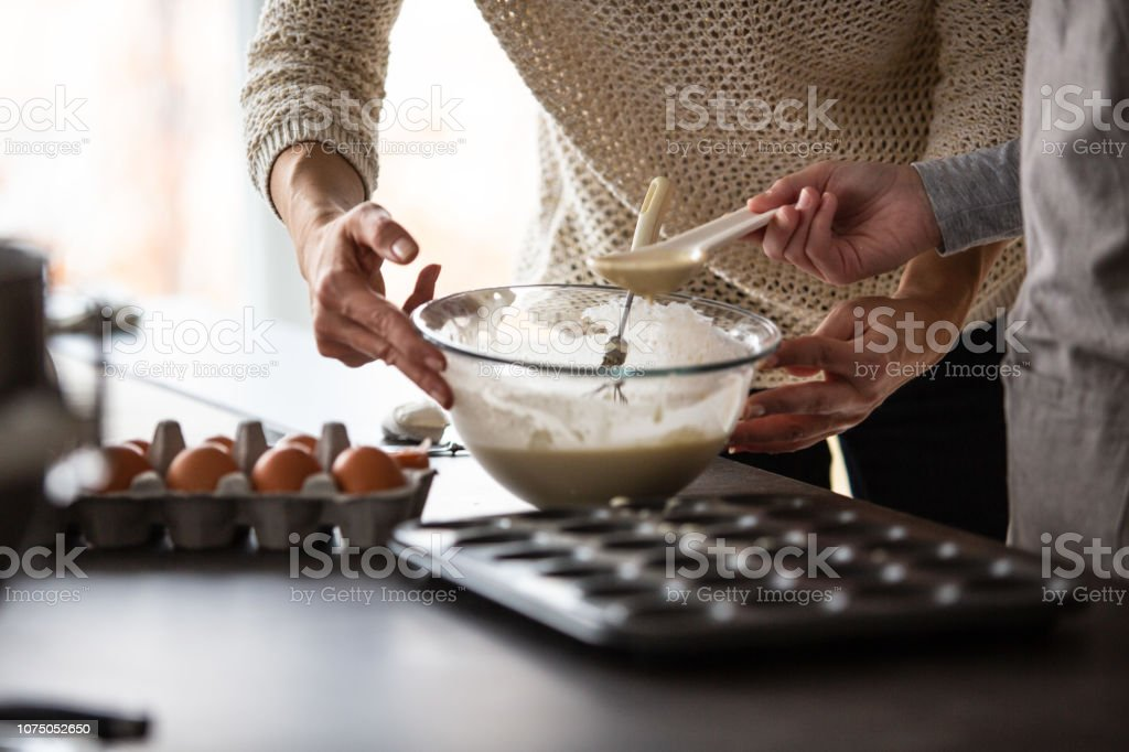 Mother and daughter baking muffins stock photo