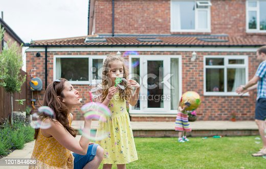 A mother and daughter are playing together in the backyard.  The are blowing bubbles.