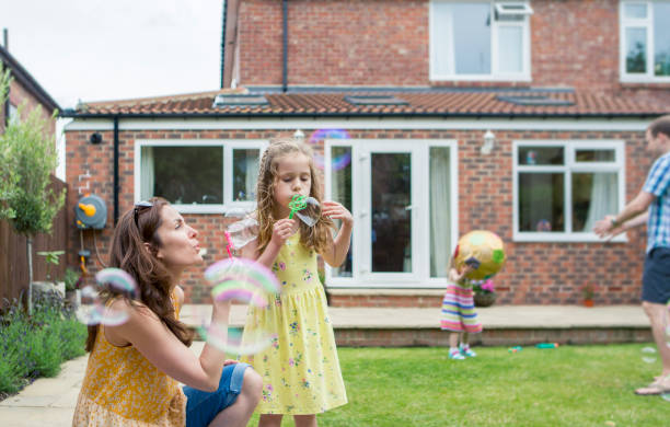 Mother and Daughter Blowing Bubbles A mother and daughter are playing together in the backyard.  The are blowing bubbles. uk stock pictures, royalty-free photos & images