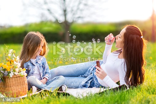 507271044istockphoto Mother and daughter blowing bubbles 519837216