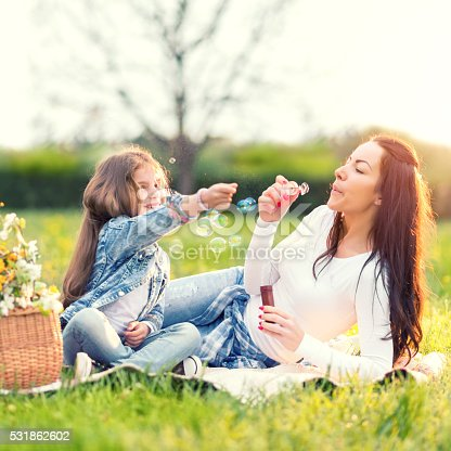 507271044istockphoto Mother and daughter blowing bubbles 531862602