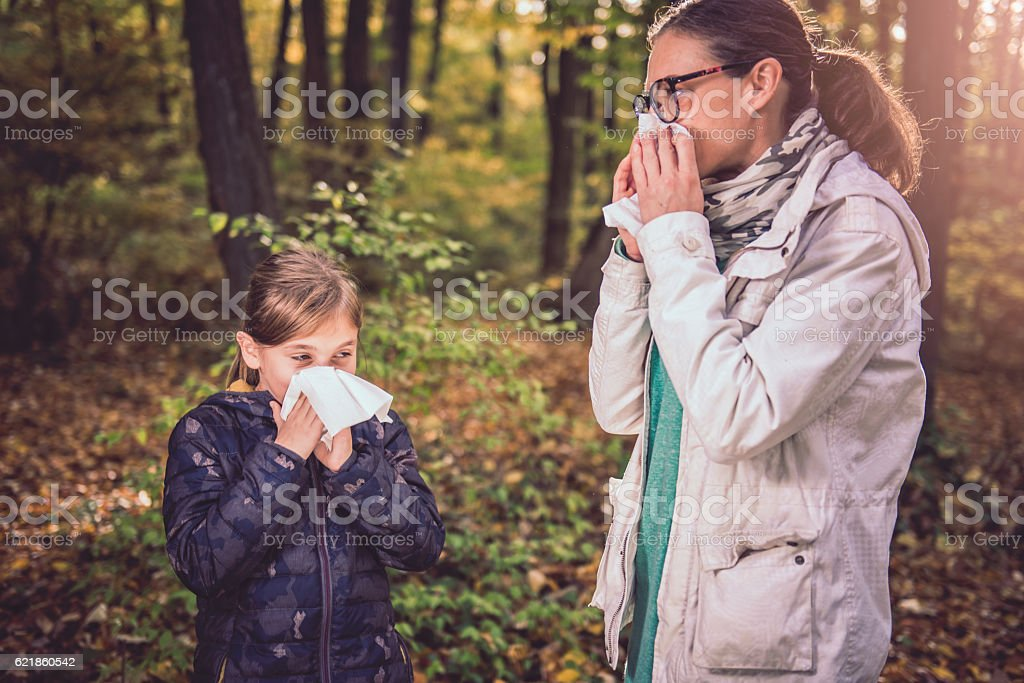 Mother and daughter blowing her nose stock photo