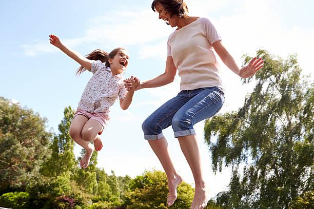 madre e hija saltando sobre trampolín juntos - trampolín artículos deportivos fotografías e imágenes de stock