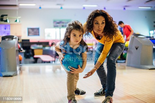 Young woman at the bowling alley with her toddler daughter