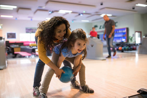 Mother and daughter bowling Woman at the bowling alley with daughter ten pin bowling stock pictures, royalty-free photos & images