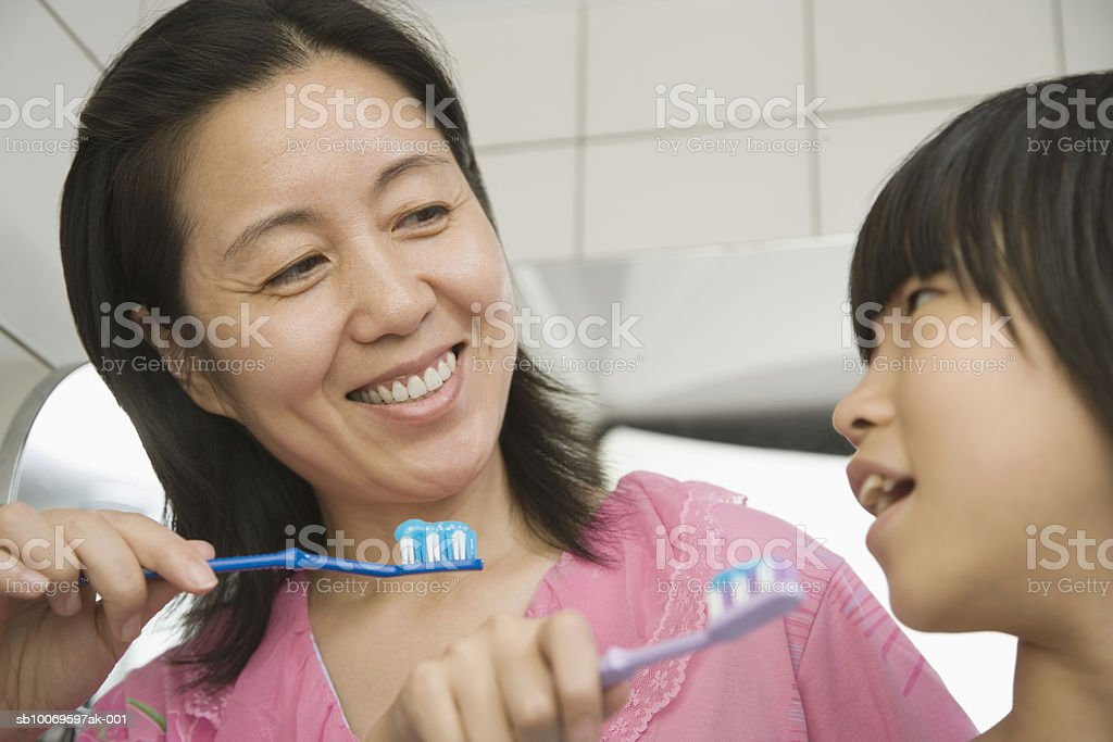 Mother and daughter (10-11) brushing teeth, low angle view royalty-free stock photo