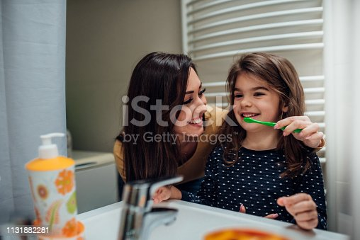 istock Mother and daughter brushing teeth 1131882281